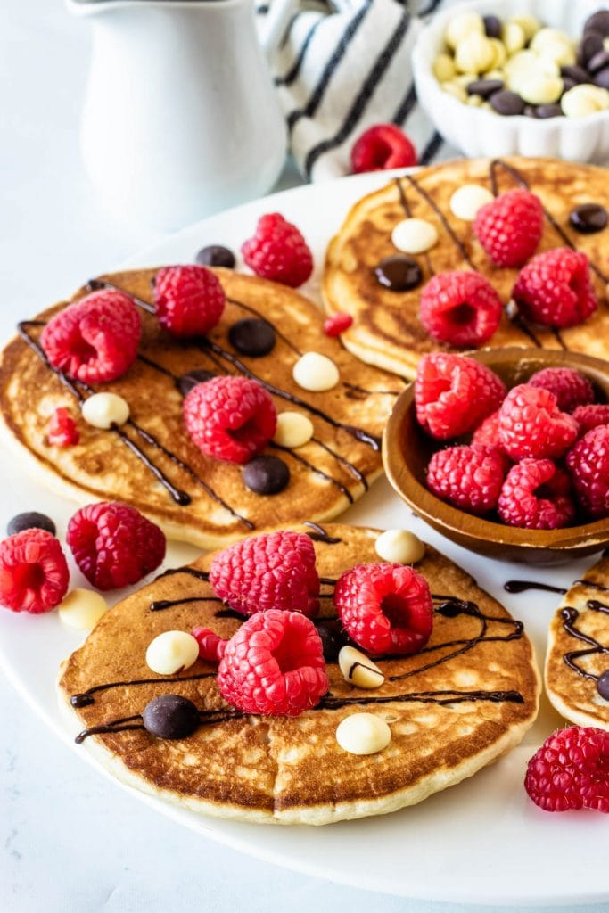 Sourdough Banana Pancakes topped with chocolate drizzle and raspberries