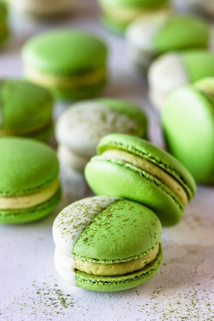green macarons dipped in white chocolate and topped with matcha powder.