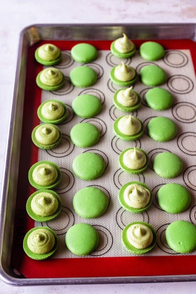 green macaron shells filled with white chocolate matcha ganache and matcha buttercream.