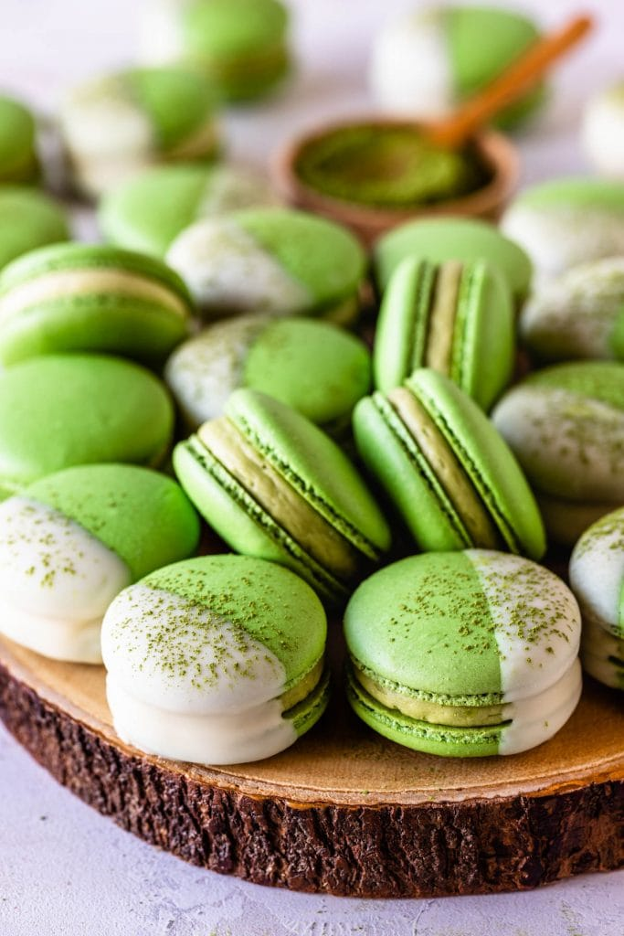 green tea Macarons dipped in white chocolate topped with matcha powder.