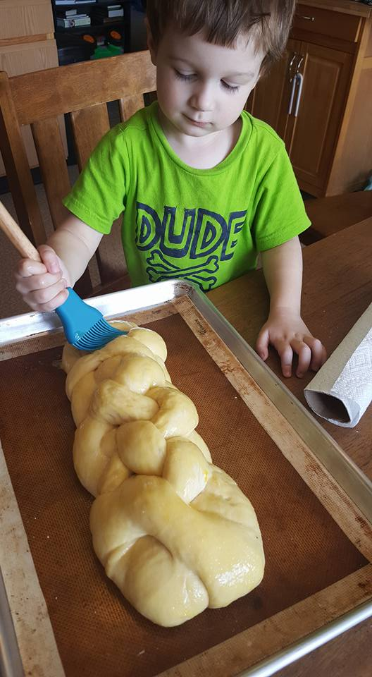 brushing challah bread with egg wash