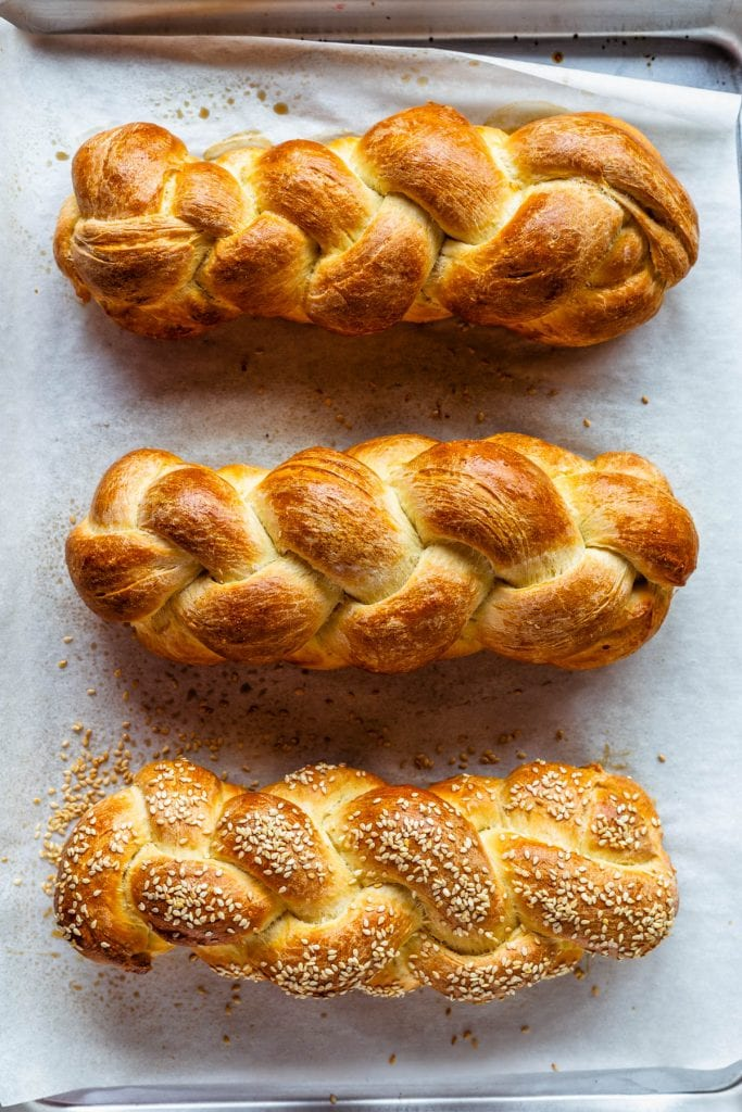 3 loaves of challah, two plain and one topped with sesame seeds.