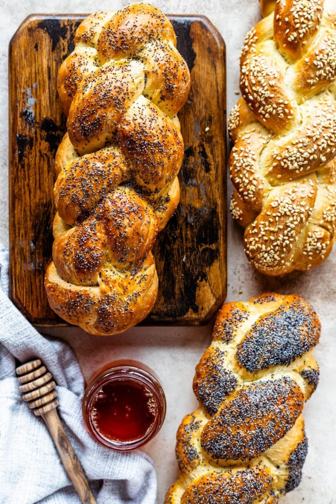 3 loaves of challan, two topped with poppy seeds and one topped with sesame seeds, with a container of honey and a honey spoon.