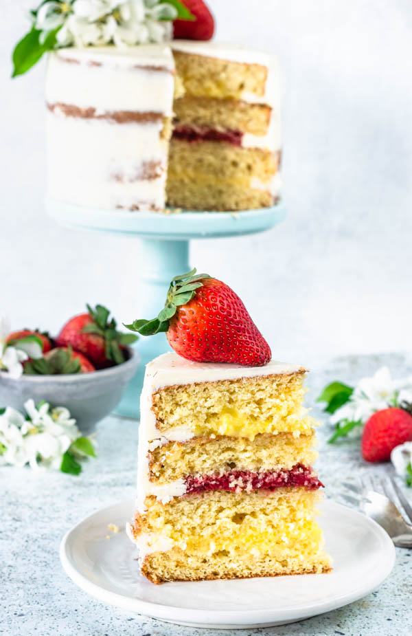 Pineapple and Strawberry layer cake topped with fresh flowers slice of cake