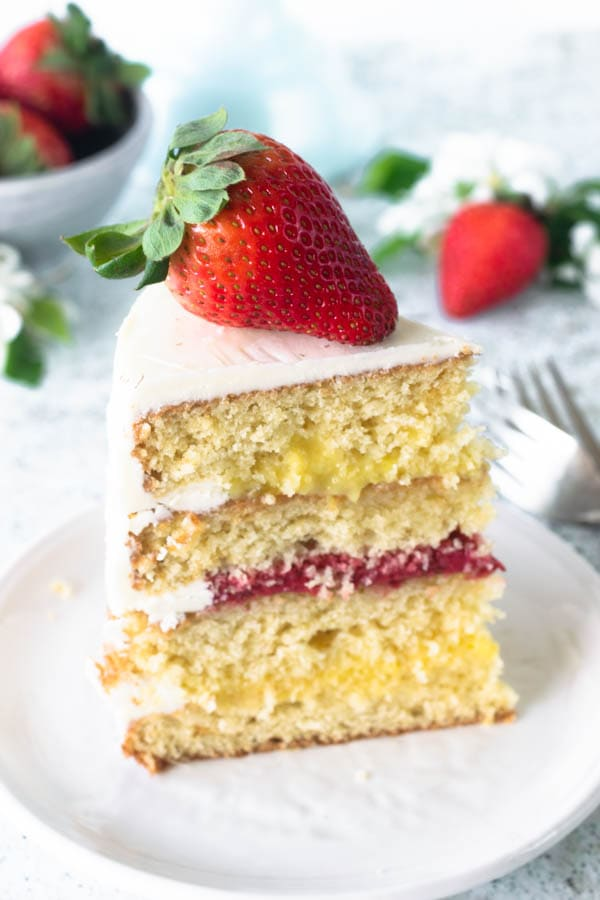 slice of Pineapple and Strawberry layer cake topped with fresh flowers