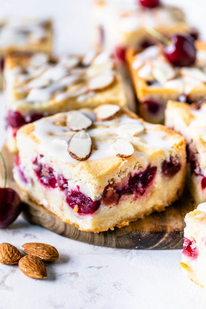 almond cherry bars topped with glaze and sliced almonds