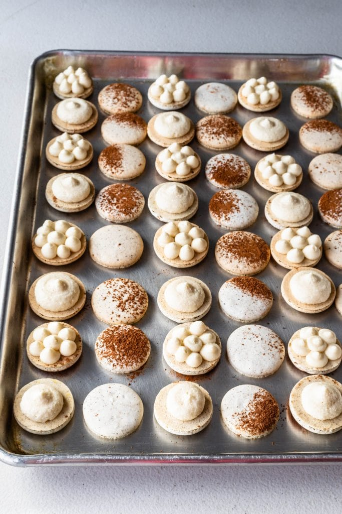 macaron shells dusted with cocoa powder filled with mascarpone frosting