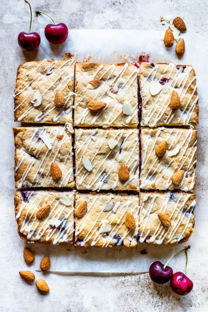 Almond cherry bars topped with almond glaze and almonds, sliced viewed from the top