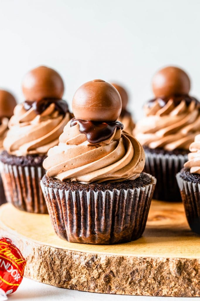 Chocolate cupcakes topped with chocolate swiss meringue buttercream and ganache and a lindt truffle on a wooden board