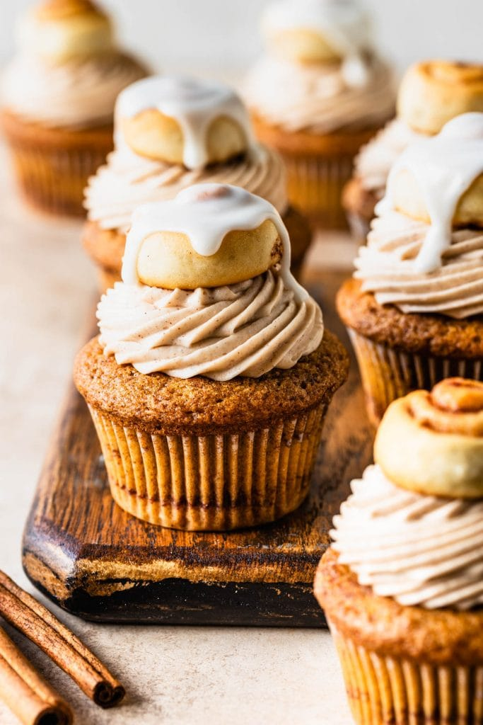 Cinnamon Roll Cupcakes topped with a glazed mini cinnamon roll on top of a wooden board.