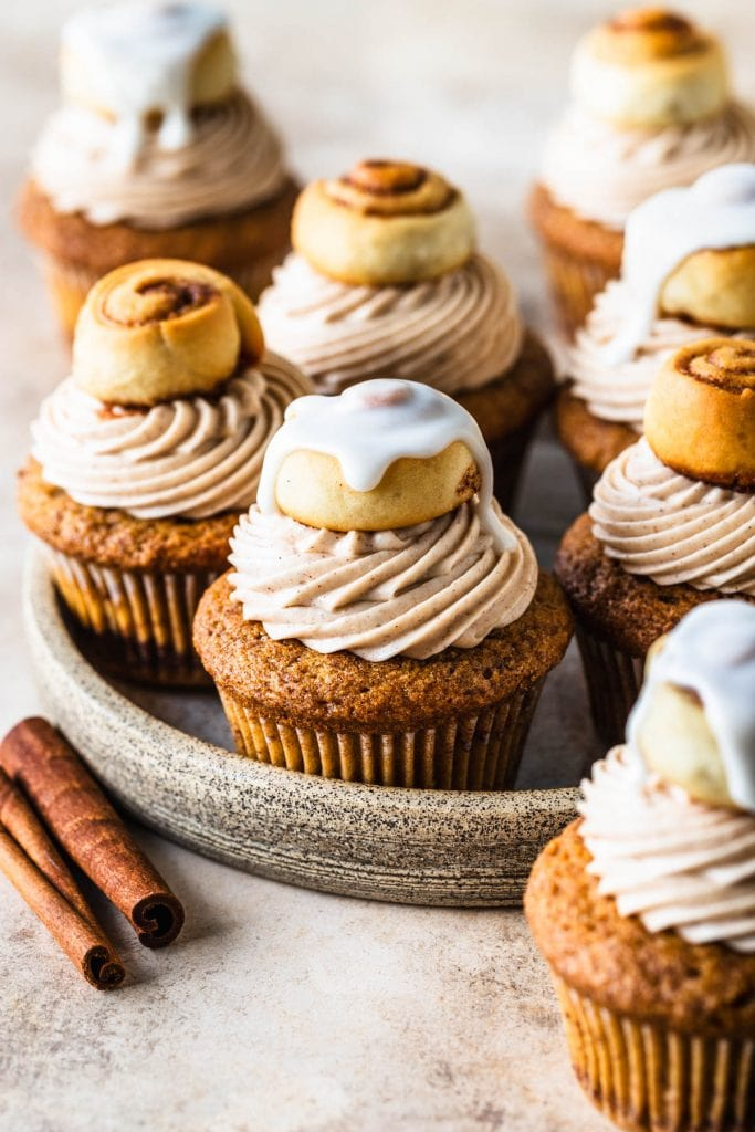 Cinnamon Roll Cupcakes topped with cinnamon rolls, some with frosting on top, and some without.