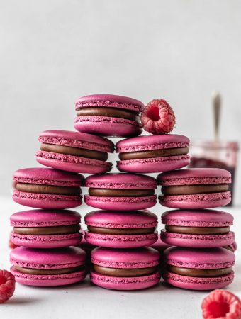 pink macarons with chocolate filling stacked with raspberries on top.