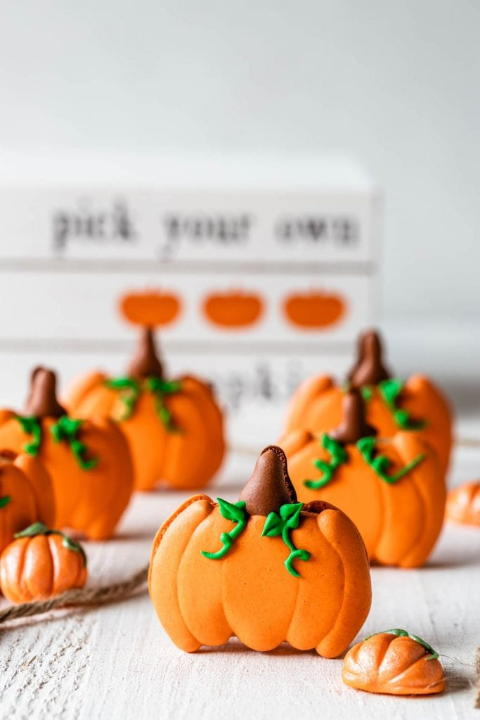 macarons shaped like pumpkins with a wooden box on the back saying: pick your own pumpkins.