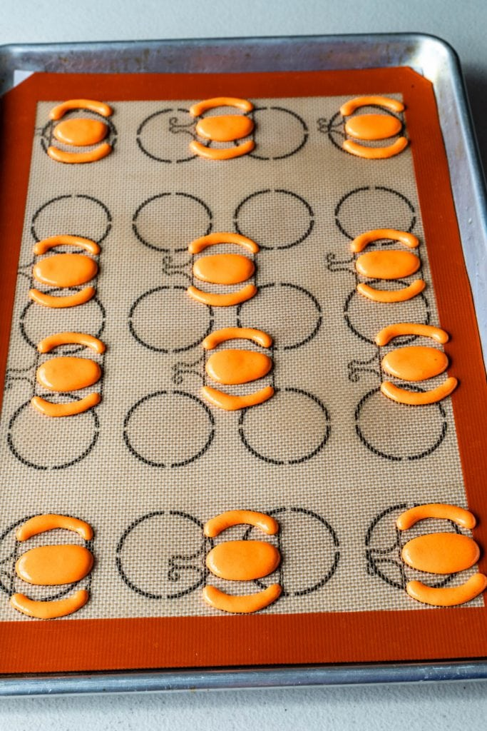 piping orange macaron batter on top of baking mat with a pumpkin macaron template underneath.