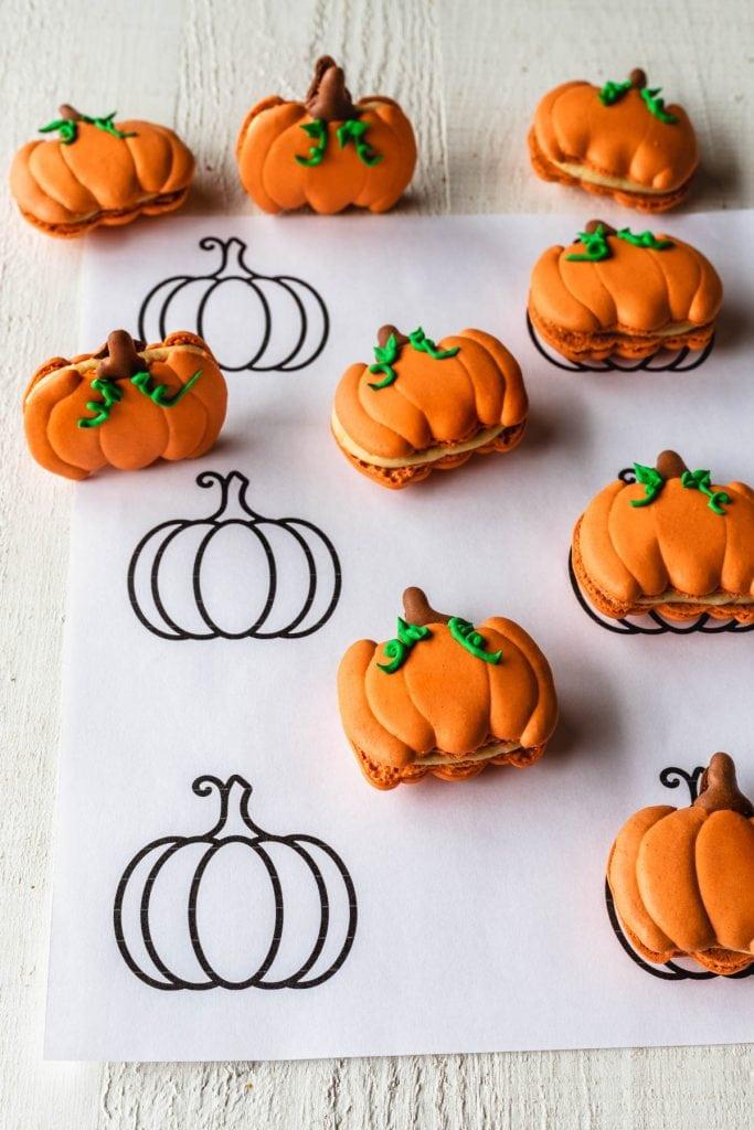 Template to make pumpkin macaron recipe, with some macarons shaped like pumpkins on top.