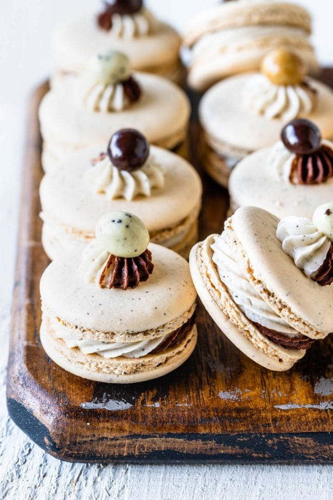 coffee macarons filled with a swirled frosting and topped with chocolate covered espresso bean on top of a wooden board.