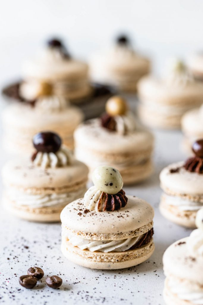 coffee macarons filled with a swirled frosting and topped with chocolate covered espresso bean.