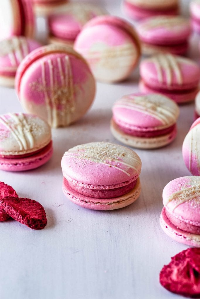 pink and white macaron shells with two color shells drizzled with white chocolate and topped with graham cracker crumb.
