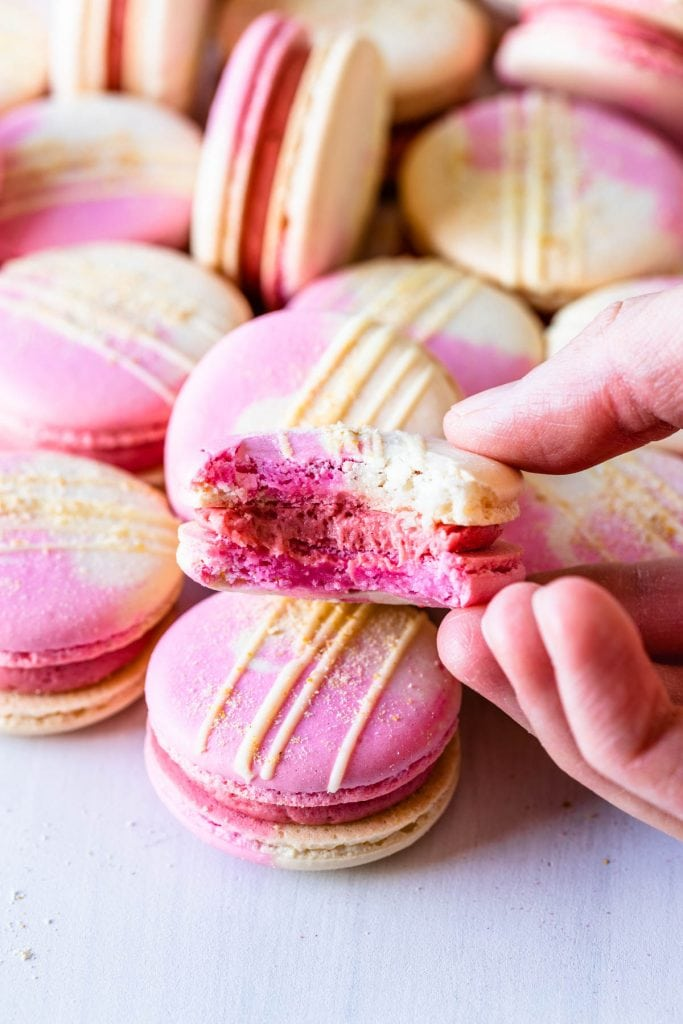 strawberry macaron with a bite taken out.