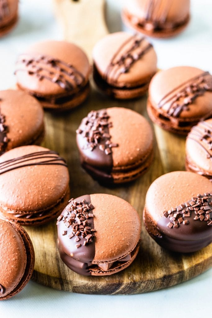 chocolate macarons filled with chocolate buttercream on a wooden board, drizzled with chocolate, or dipped in chocolate and topped with sprinkles