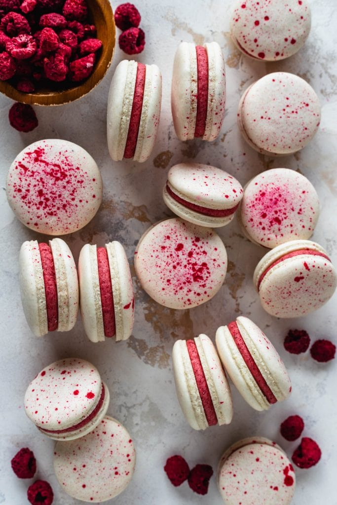 vegan macarons filled with pink raspberry frosting topped with speckles, surrounded by freeze dried raspberries.