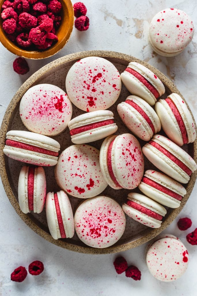 Vegan Raspberry Macarons with a speckled pink shell, filled with pink frosting.