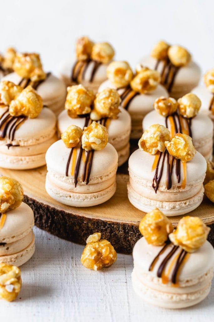 Caramel Popcorn Macarons filled with caramel buttercream and topped with caramel popcorn.