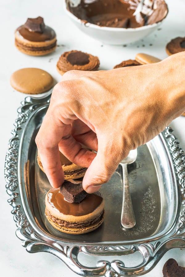 placing brownie heart on top of chocolate macaron