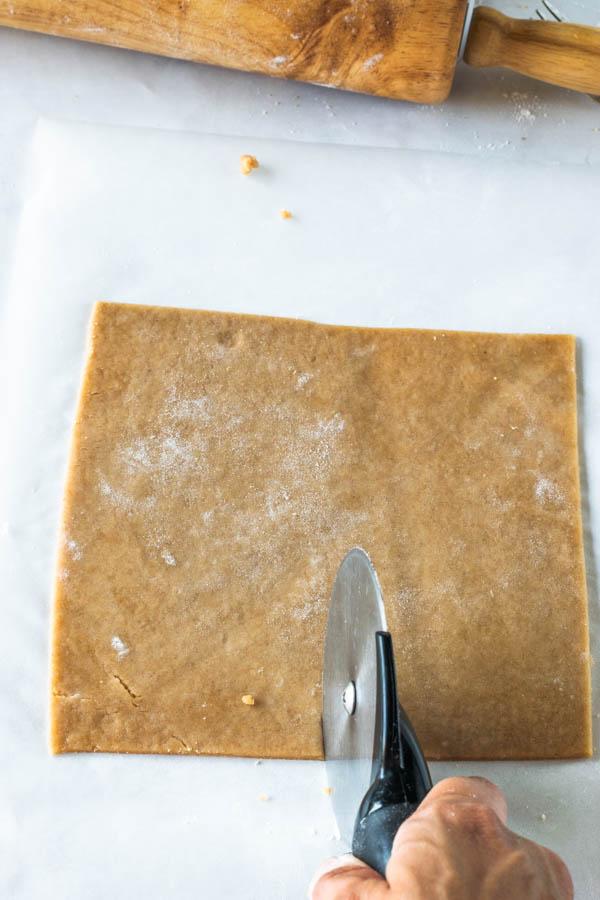 pizza cutter cutting dough