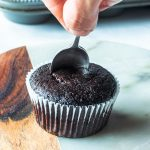 removing the center of a chocolate cupcake with a spoon