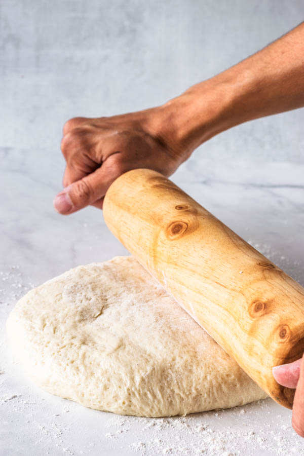rolling vegan donut dough with a rolling pin