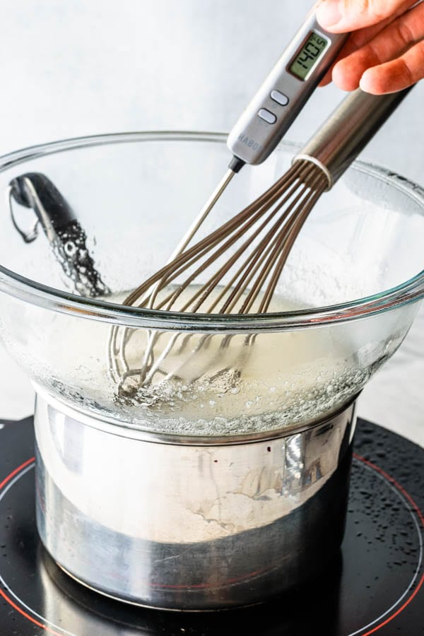 taking temperature of egg white and sugar syrup for swiss meringue