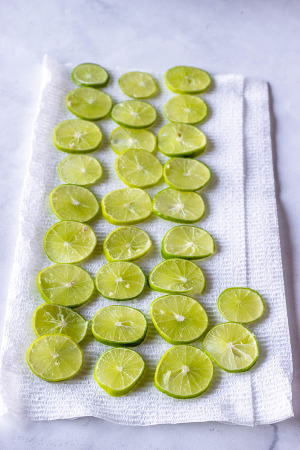key lime slices draining on a sheet of paper