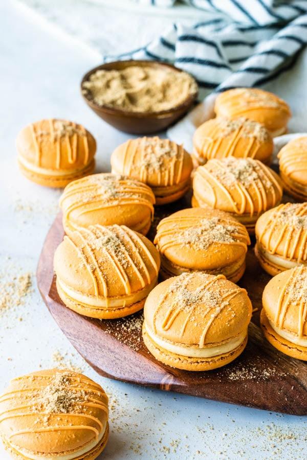 Pumpkin Cheesecake Macarons on a wooden board