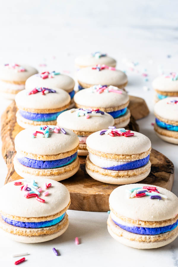 Vegan Vanilla Macarons with Sprinkles and multi-color buttercream on a wooden board