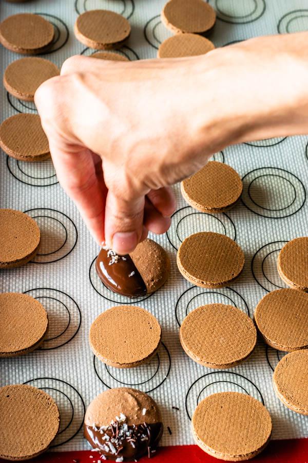 sprinkling coconut flakes on top of chocolate macaron shells