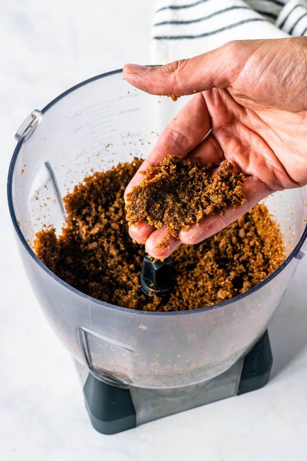 holding some vegan cookie crumbs to make vegan cheesecake crust