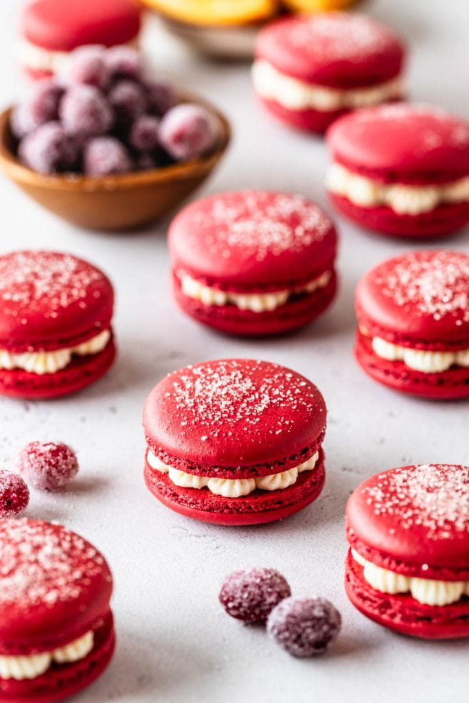 cranberry macarons with dusting of sugar on top and sugared cranberries behind.