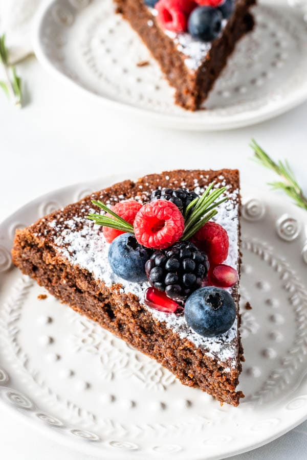 slice of flourless Olive Oil Chocolate Cake dusted with powdered sugar and topped with fresh berries