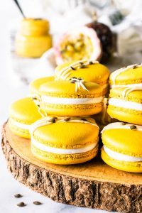 Passion Fruit Macarons filled with passion fruit curd and marshmallow frosting topped with white chocolate and passion fruit seeds