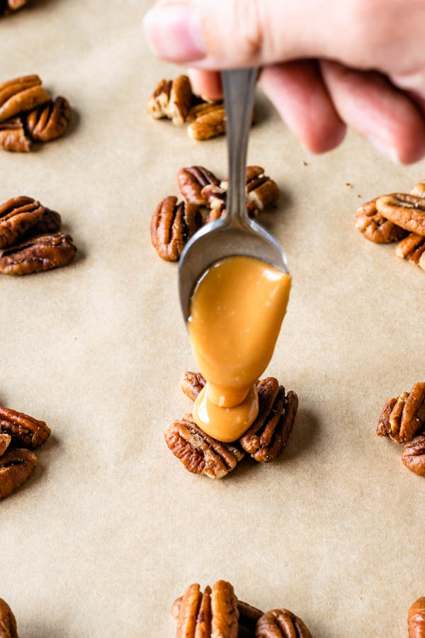 pouring caramel over clusters of pecan