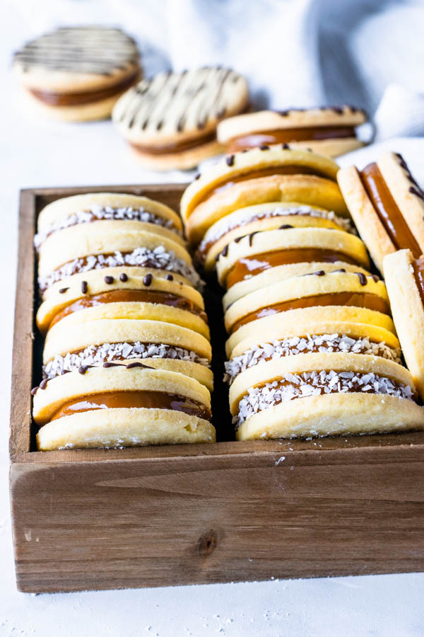 Alfajor Cookies filled with dulce de leche drizzled with melted chocolate and coated in coconut