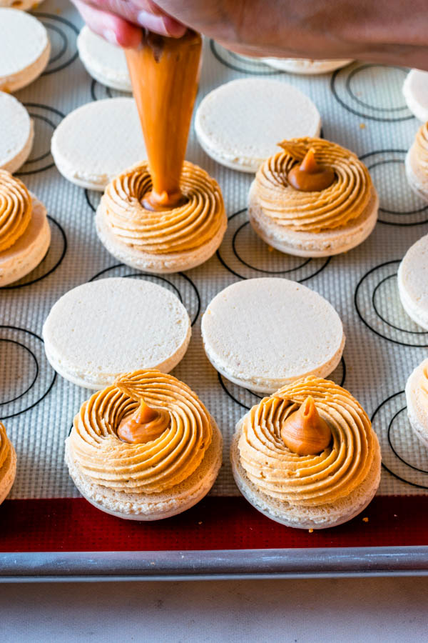 piping butterscotch ganache in the center of Butterbeer Macarons