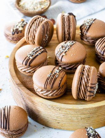 Nutella Macarons with chocolate drizzled on top and chopped hazelnuts