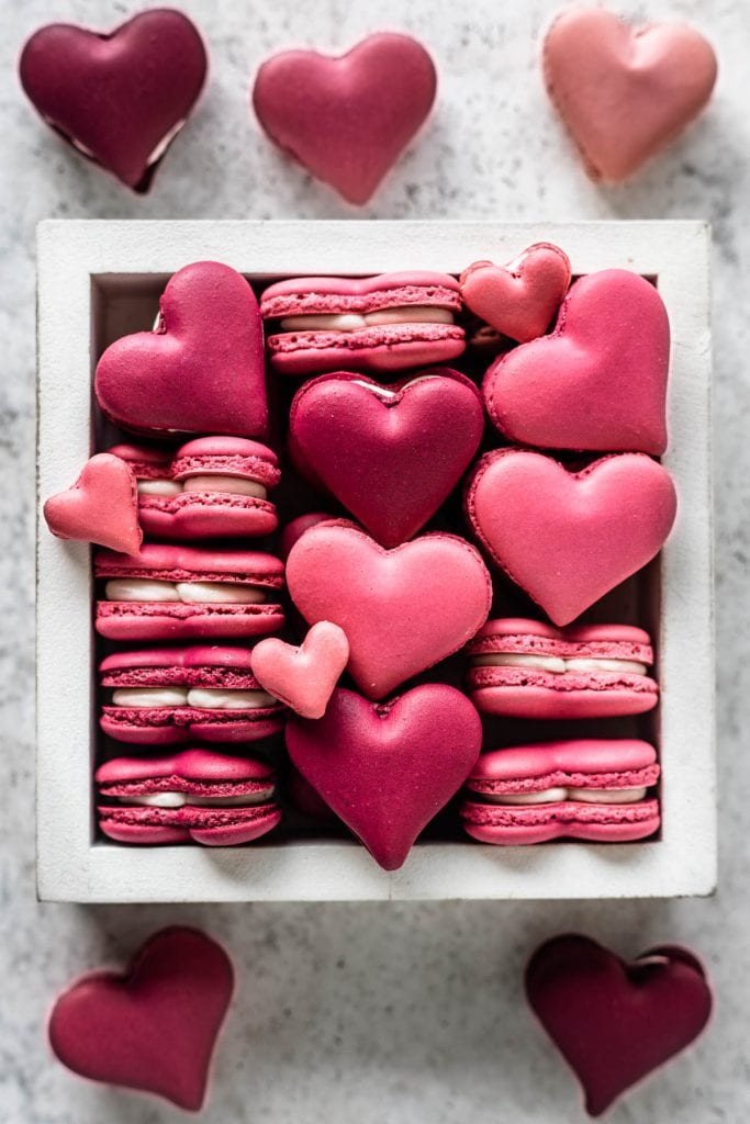 burgundy and pink Heart Macarons in a small plate.