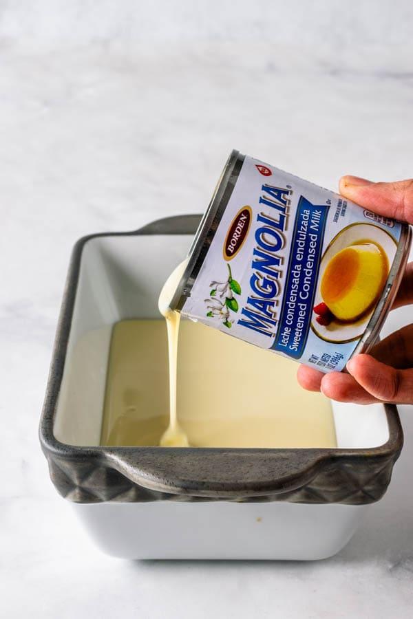 pouring condensed milk in a dish to make dulce de leche