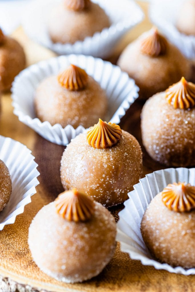 dulce de leche truffles as known as churros brigadeiros in paper cups on top of a wooden board.