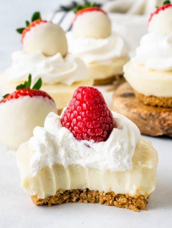 No-Bake White Chocolate Cheesecake bite topped with whipped cream and raspberries