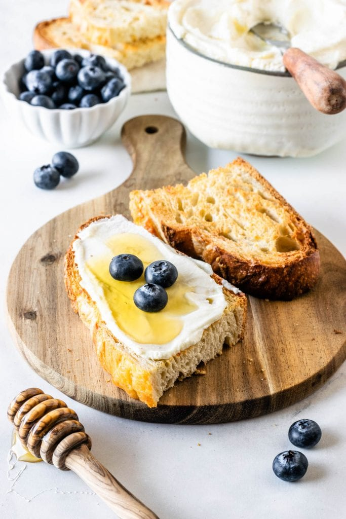Homemade Ricotta Cheese spread on toast with honey and blueberries