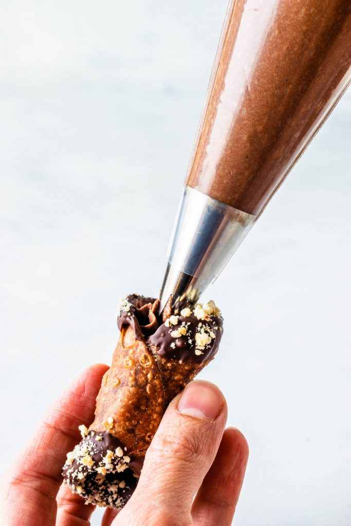 piping chocolate filling on chocolate cannolo